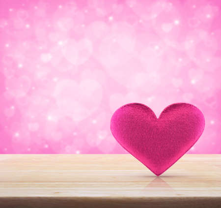 day light: Fabric pink heart shape on wooden table over light pink heart bokeh background, valentine concept