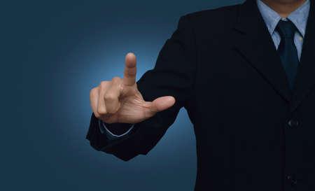 Zakenman wijzend naar iets of een touch screen op een blauwe achtergrond te raken Stockfoto