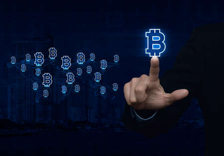 Businessman pressing bitcoin icon with light blue world map connection on city tower, Choosing bitcoin concept