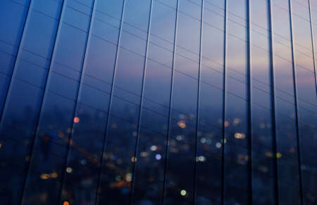 metal wall: Reflection of blurred aerial view of cityscape on warm light sundown in metal wall of office building