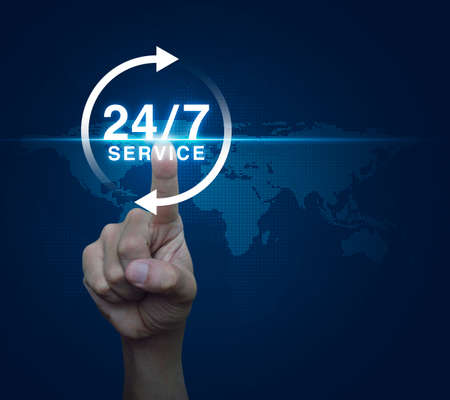 Hand pressing button 24 hours service icon over digital world map blue background, Full time service concept