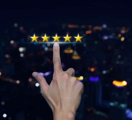 Hand click on five yellow stars to increase rating over blurred light city tower background, Feedback concept Stockfoto