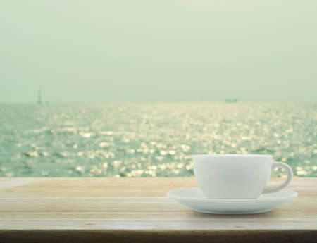 green tone: White cup on wooden table with blurred sea waves with bokeh light, green tone Stock Photo