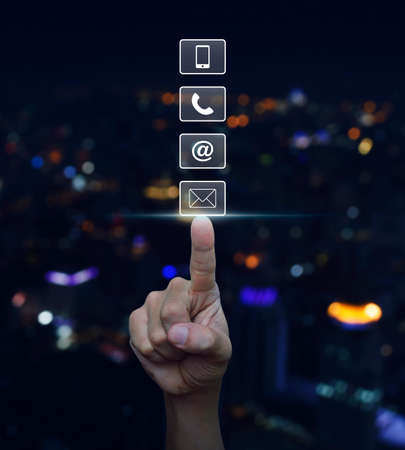 Hand pressing telephone, mobile phone, at and email buttons over blurred light city tower background, Customer support concept Stockfoto