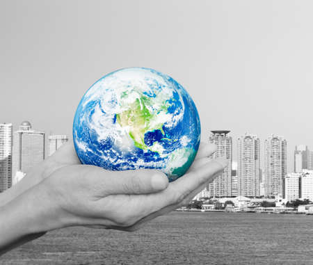 earth handful: Earth in black and white hands over city tower and river background, Environment concept