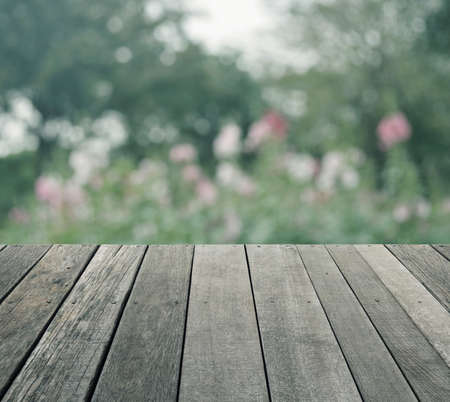 old wood floor: Empty old wood floor with blurred of pink flower and tree in public park, soft tone