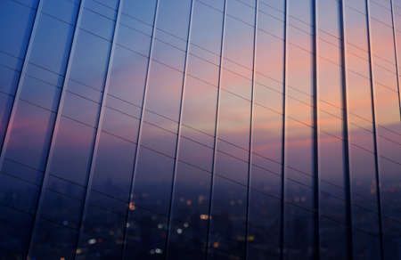 building business: Reflection of blurred aerial view of cityscape on warm light sundown in metal wall of office building