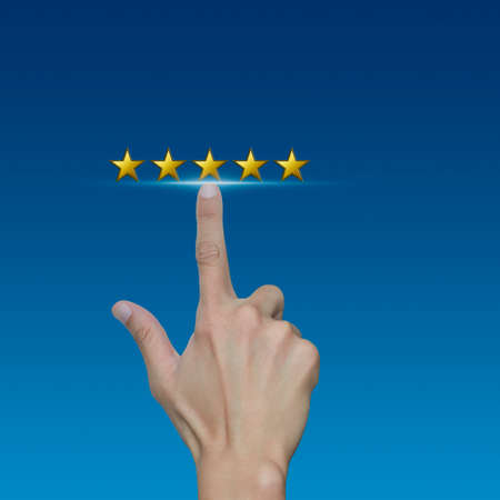 five stars: Hand click on five gold stars to increase rating on blue background, Feedback concept Stock Photo
