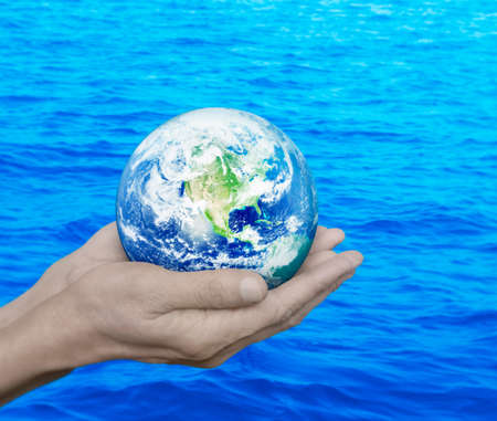 earth handful: Earth in hands over blue sea background, Environment concept