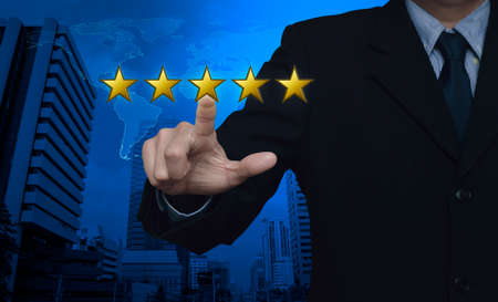 five stars: Businessman pressing five gold stars to increase rating over map and city tower, Feedback concept Stock Photo