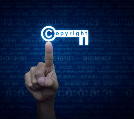 patents: Hand pressing copyright key icon over computer binary code blue background, Copyright and patents concept