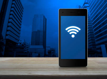 wireless hot spot: Wi-fi connection icon on modern smart phone screen on wooden table over city tower background, Technology and internet concept