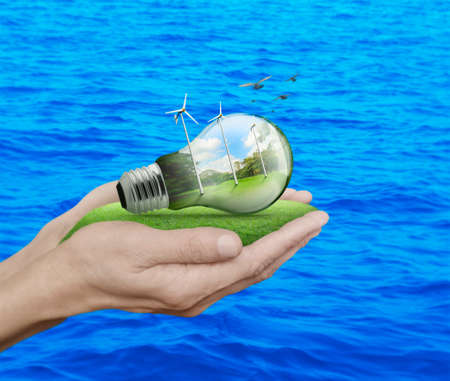 water turbine: Light bulb with wind turbines, birds and forest inside in hands over blue sea background, Ecological concept