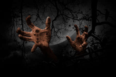 rising dead: Zombie hand rising out from old fence over dead tree, crow, moon and cloudy sky, Spooky background, Halloween concept