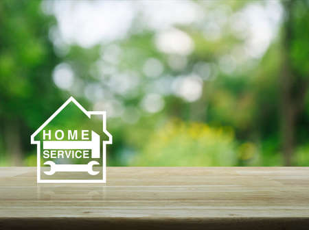 tree service: Hammer and wrench with house icon on wooden table over blur green tree background, Home service concept