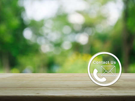 Telephone and mail icon button on wooden table over blur green tree background, Contact us concept