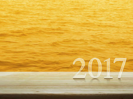 Happy new year 2017 text on wooden table over gold water sea surface texture