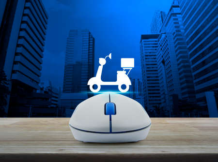 Wireless computer mouse with motor bike icon on wooden table over modern city tower, Business internet delivery service concept