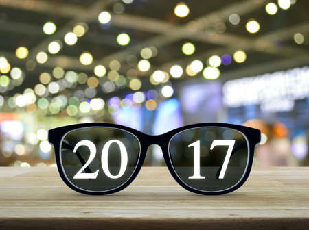 2017 text with eye glasses on wooden table over blur light and shadow of shopping mall, Business vision concept Standard-Bild