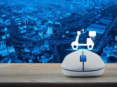 Wireless computer mouse with motor bike icon on wooden table over aerial of city tower, street and expressway, Business internet delivery service concept Stock Photo