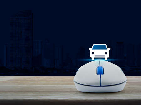 Wireless computer mouse with car front view flat icon on wooden table over city tower, Internet service car concept Stock Photo