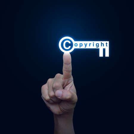patents: Hand pressing copyright key icon on blue background, Copyright and patents concept