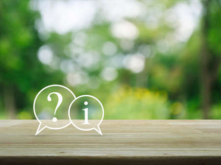 Question mark and information chat icon on wooden table over blur green tree background, Customer support concept