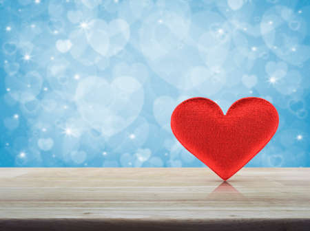 Fabric red love heart on wooden table over blur blue background, Valentines day concept Stock Photo