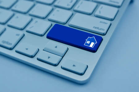 House icon on modern computer keyboard button, Real estate concept, blue tone