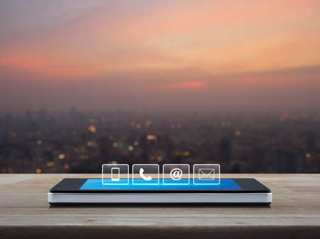 Telephone, mobile phone, at and email buttons on modern smart phone screen on wooden table over blur of cityscape on warm light sundown, Customer support concept