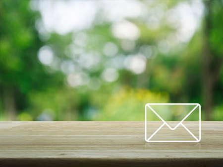 icono de correo en la mesa de madera sobre el árbol verde borroso en el jardín, Contacto concepto Foto de archivo