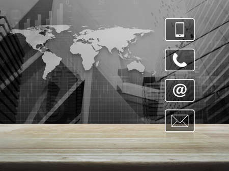 Telephone, mobile phone, at and email buttons on wooden table over world map with financial graph and city tower, Customer support concept Stockfoto