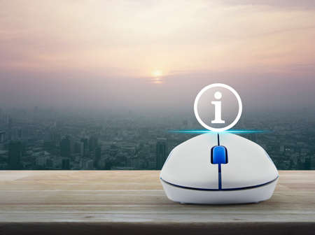 advise: Information sign icon with wireless computer mouse on wooden table over modern city tower at sunset, vintage style, Customer support concept