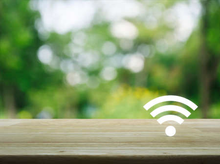 Wi-fi button on wooden table over blur green tree in park, Technology and internet concept Imagens