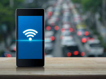 Wi-fi connection icon on modern smart phone screen on wooden table over blur of rush hour with cars and road, Technology and internet concept