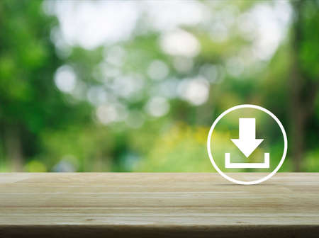 Download icon on wooden table over blur green tree in park, Business internet concept