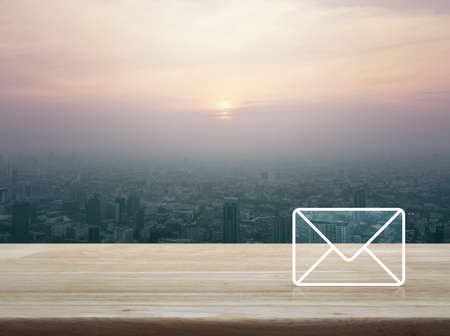 Mail icon on wooden table over city tower at sunset, vintage style, Contact us concept