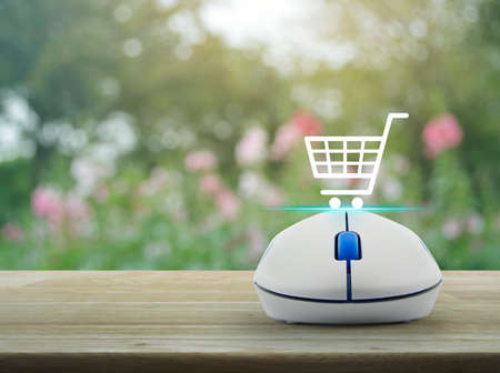 Shopping basket icon with wireless computer mouse on wooden table over blur pink flower and tree, vintage style, Shop online concept