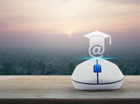 Wireless computer mouse with e-learning icon on wooden table over modern city tower at sunset, vintage style, Study online concept Banque d'images