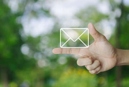 Mail icon on finger over blur green tree background, Contact us concept Stock Photo
