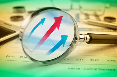 Rising red and blue arrow on magnifying glass over graph, Success business concept Stock Photo