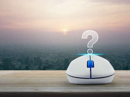 Question mark sign icon with wireless computer mouse on wooden table over modern city tower at sunset, vintage style, Customer support concept