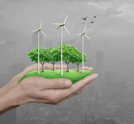 Wind turbines, grass and trees in human hands over pollution city, Ecological concept Stock Photo