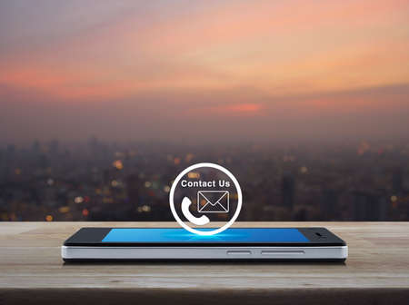 customer support: Telephone and mail icon button on modern smart phone screen on wooden table over blur of cityscape on warm light sundown, Contact us concept