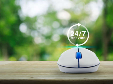 24: 24 hours service icon with wireless computer mouse on wooden table over blur green tree in park, Full time service concept Stock Photo