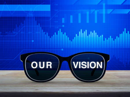 Black glasses with our vision text on wooden table over financial graph and chart, Business concept