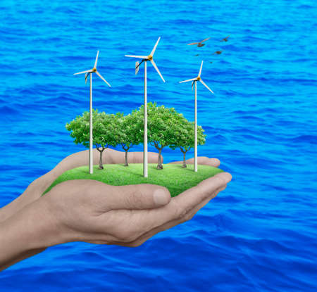 Wind turbines, grass and trees in human hands over blue sea, Ecological concept