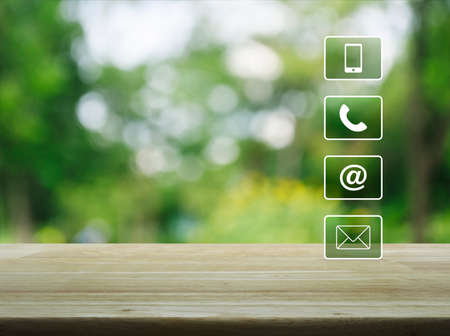 Telephone, mobile phone, at and email buttons on wooden table over blur green tree background, Customer support concept