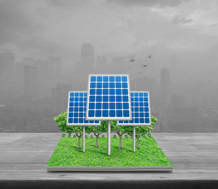Solar cell from open book on wooden table over pollution city tower, Ecology concept
