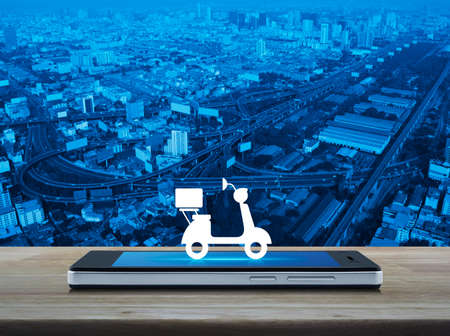 Motor bike icon  on modern smart phone screen on wooden table over city tower, street and expressway, Business delivery service concept